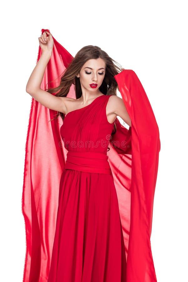 mujer atractiva que presenta en vestido rojo con velo de la gasa imagenes de archivo
