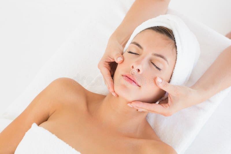 Mujer atractiva que recibe masaje facial en el centro del balneario fotografía de archivo