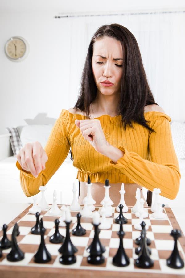 Mujer atractiva que se sienta delante del ajedrez - dificultades de sensación fotos de archivo libres de regalías