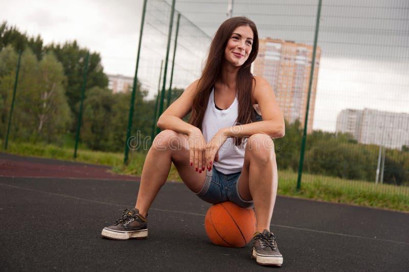 Mujer atractiva que se sienta en baloncesto imagenes de archivo