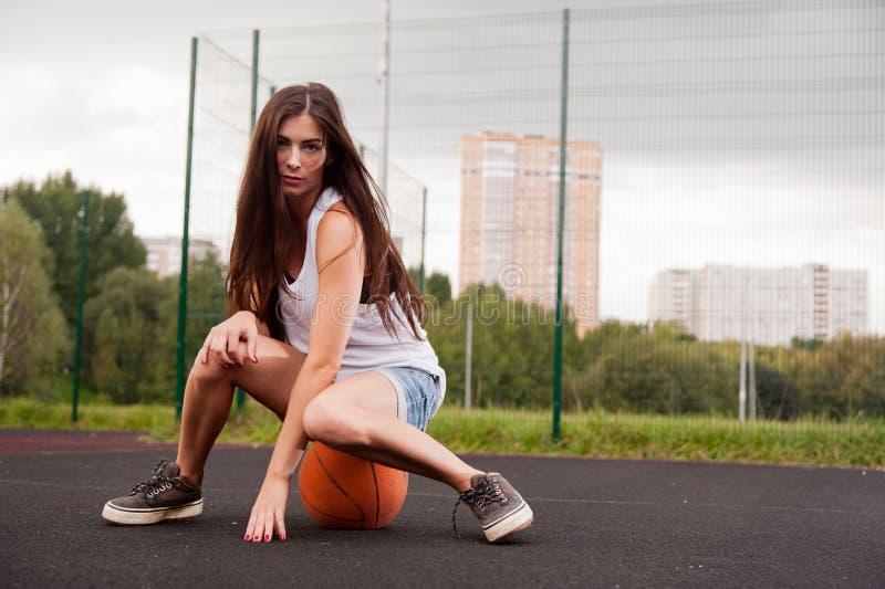 Mujer atractiva que se sienta en baloncesto fotos de archivo