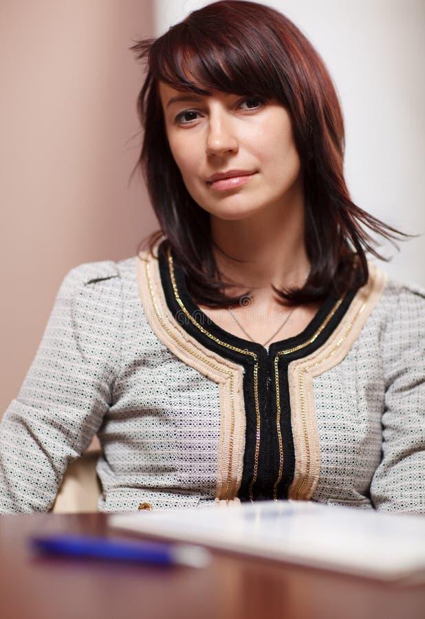 Mujer atractiva que se sienta en la oficina fotografía de archivo libre de regalías