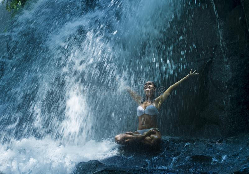 Mujer atractiva que se sienta en la roca en la actitud de la yoga para la serenidad y la meditación espirituales de la relajación imágenes de archivo libres de regalías