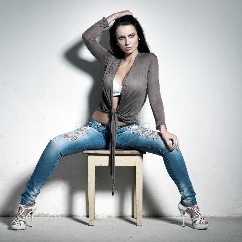 Mujer atractiva que se sienta en taburete foto de archivo
