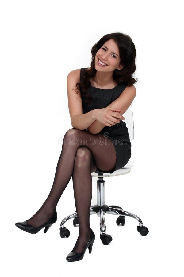 Mujer atractiva que se sienta en una silla foto de archivo libre de regalías