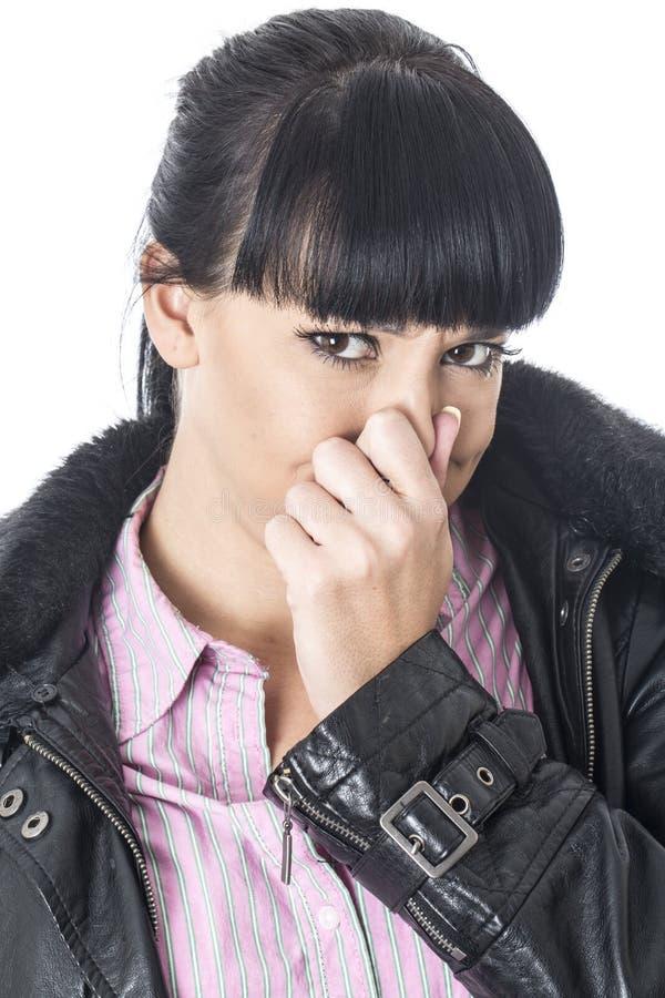 Mujer atractiva que se sostiene la nariz para parar un mún olor o un aroma fotografía de archivo libre de regalías