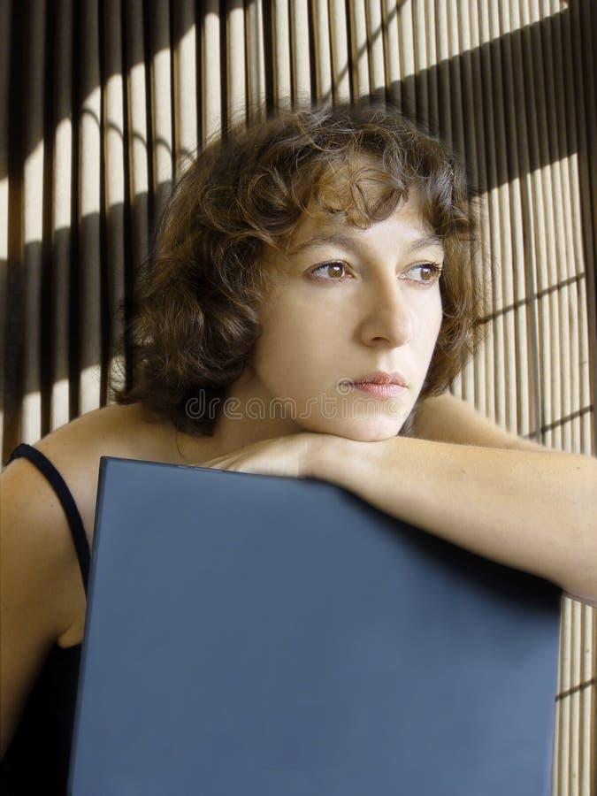 Mujer atractiva que soña despierto con la computadora portátil fotos de archivo libres de regalías
