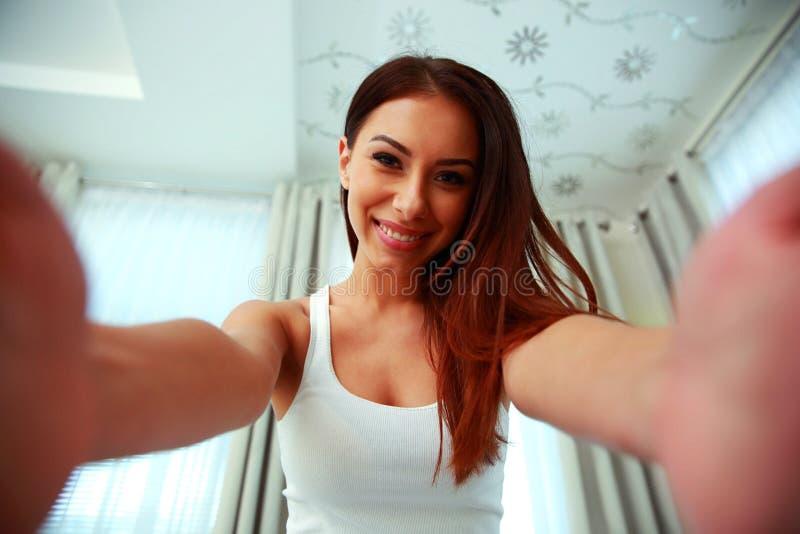 Mujer atractiva que sonríe en la cámara imagen de archivo