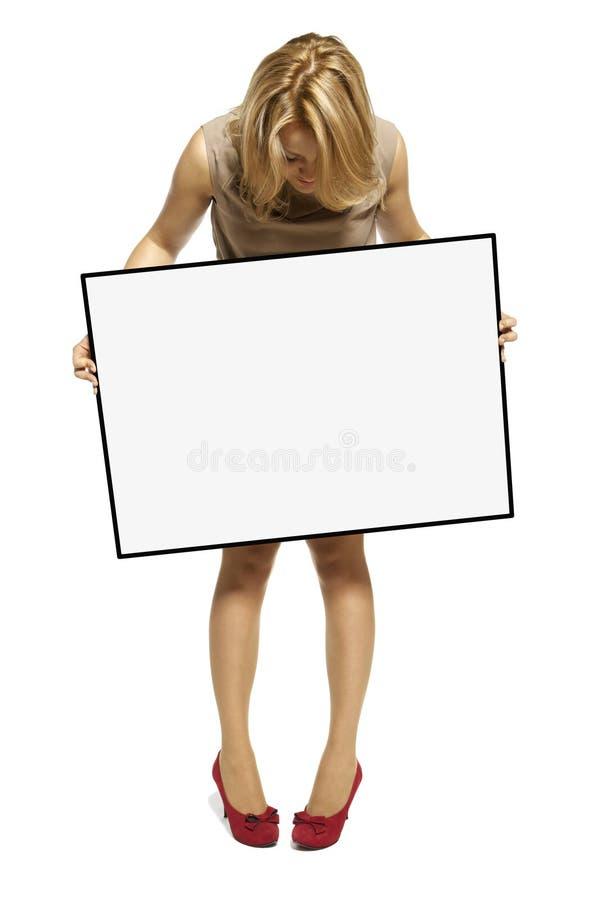 Mujer atractiva que soporta una muestra en blanco imágenes de archivo libres de regalías