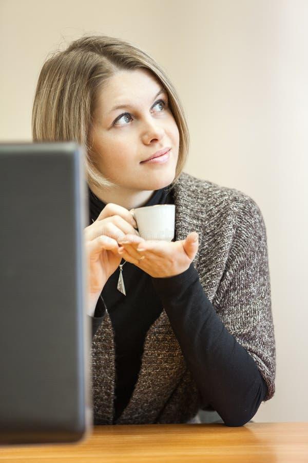 Mujer atractiva que sueña con la taza de café en el lugar de trabajo fotografía de archivo