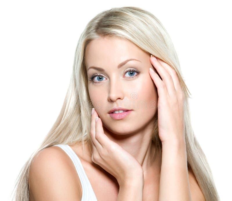 Mujer atractiva que toca su cara fresca