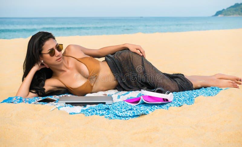 Mujer atractiva que toma el sol en la playa con el ordenador portátil, teléfono móvil mientras que se relaja fotografía de archivo