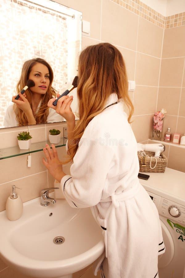 Mujer atractiva que usa el cepillo del maquillaje fotos de archivo libres de regalías