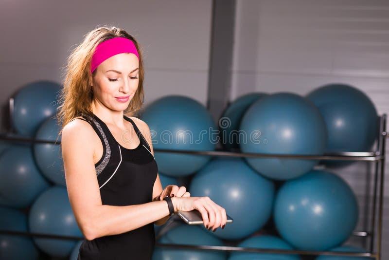 Mujer atractiva que usa el teléfono celular y al perseguidor de la aptitud en gimnasio imágenes de archivo libres de regalías