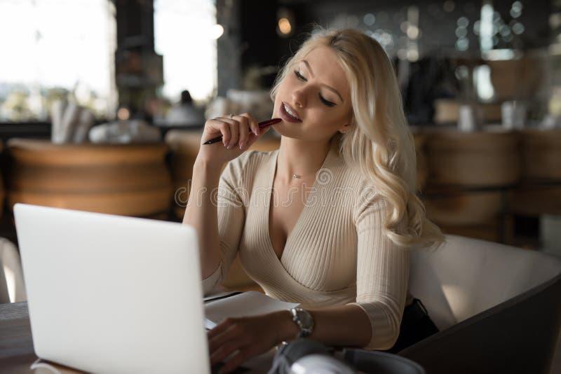 Mujer atractiva que usa la PC del ordenador portátil que se sienta en café imagen de archivo libre de regalías