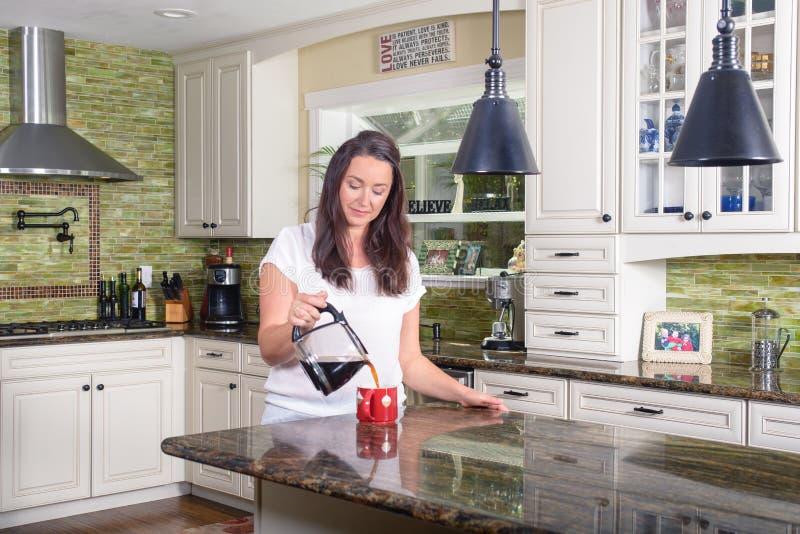 Mujer atractiva que vierte el café hecho en casa para dos en cocina soleada moderna fotos de archivo