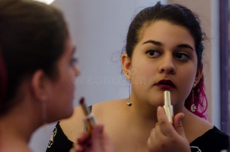 Mujer atractiva rechoncha que pone en un cierto maquillaje imagen de archivo