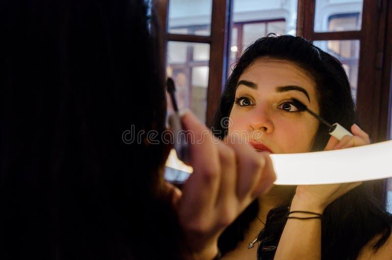 Mujer atractiva rechoncha que pone en un cierto maquillaje foto de archivo