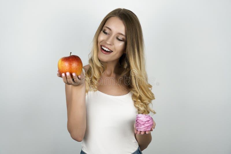 Mujer atractiva rubia sonriente que sostiene la manzana roja jugosa en una mano y magdalena sabrosa rosada en el otro blanco aisl foto de archivo libre de regalías