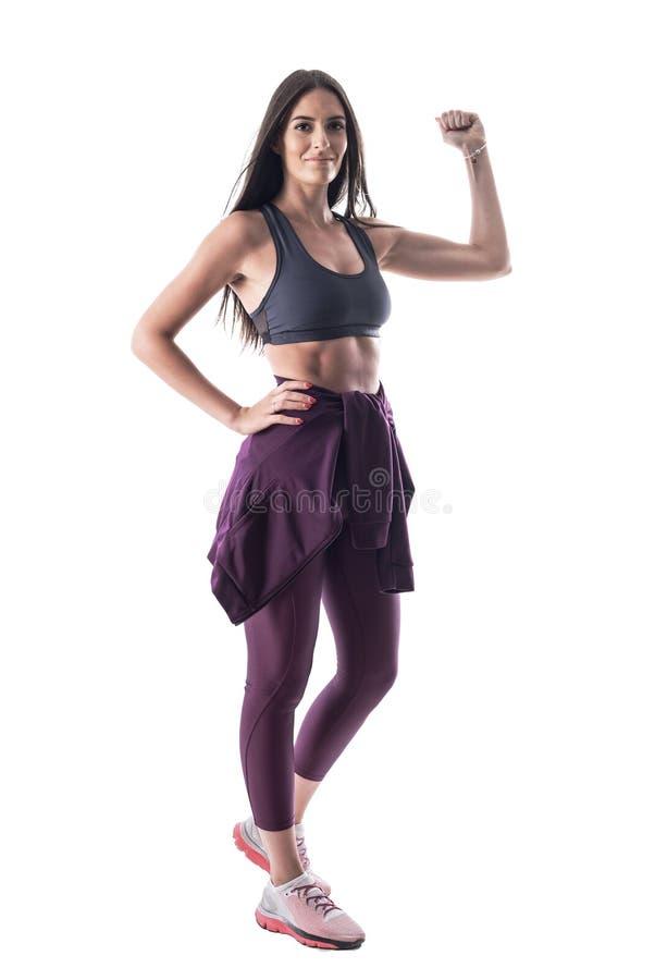 Mujer atractiva sana del ajuste joven motivado que dobla y que muestra el músculo del brazo del bíceps foto de archivo