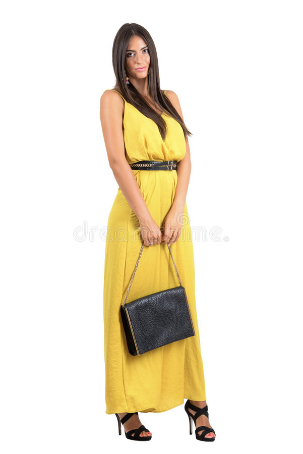 Mujer atractiva sensual en el mono amarillo que sostiene el bolso de cuero negro fotos de archivo libres de regalías