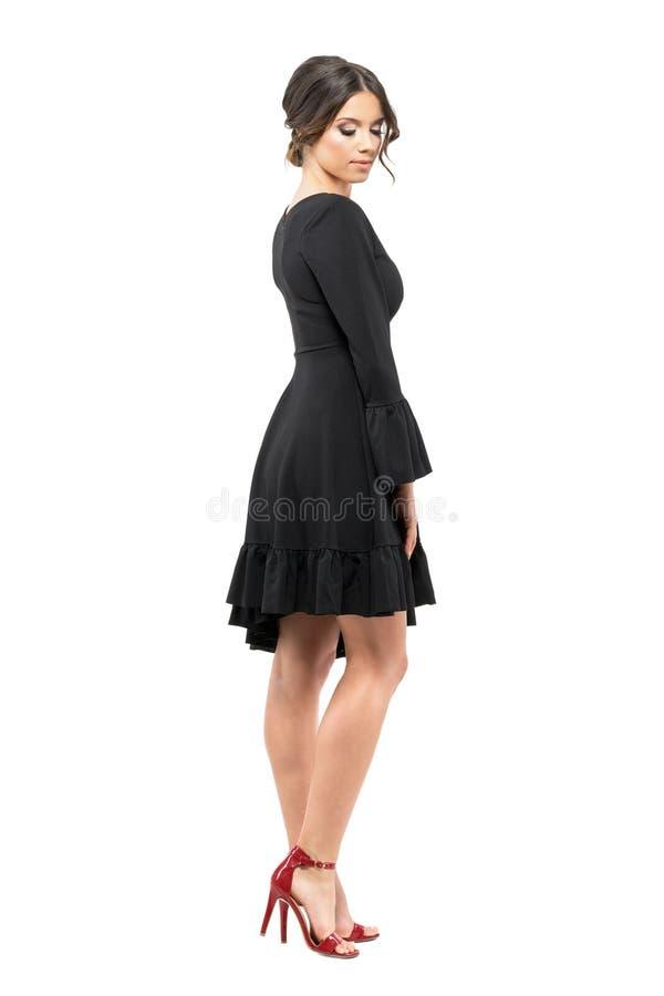 Mujer atractiva sofisticada en el vestido negro que mira abajo Vista lateral foto de archivo