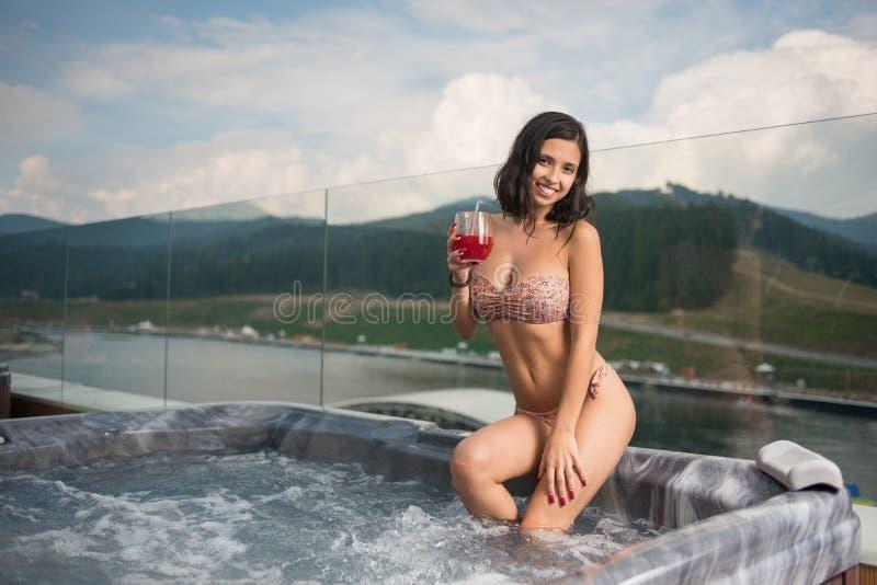Mujer atractiva sonriente con el cuerpo perfecto en el bikini que se sienta en el Jacuzzi con el cóctel y que mira a la cámara imágenes de archivo libres de regalías