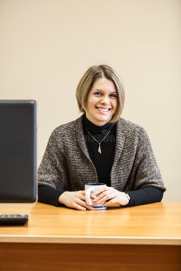 Mujer atractiva sonriente feliz con la taza en manos imagenes de archivo