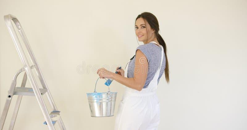 Mujer atractiva sonriente que pinta su hogar imagen de archivo libre de regalías