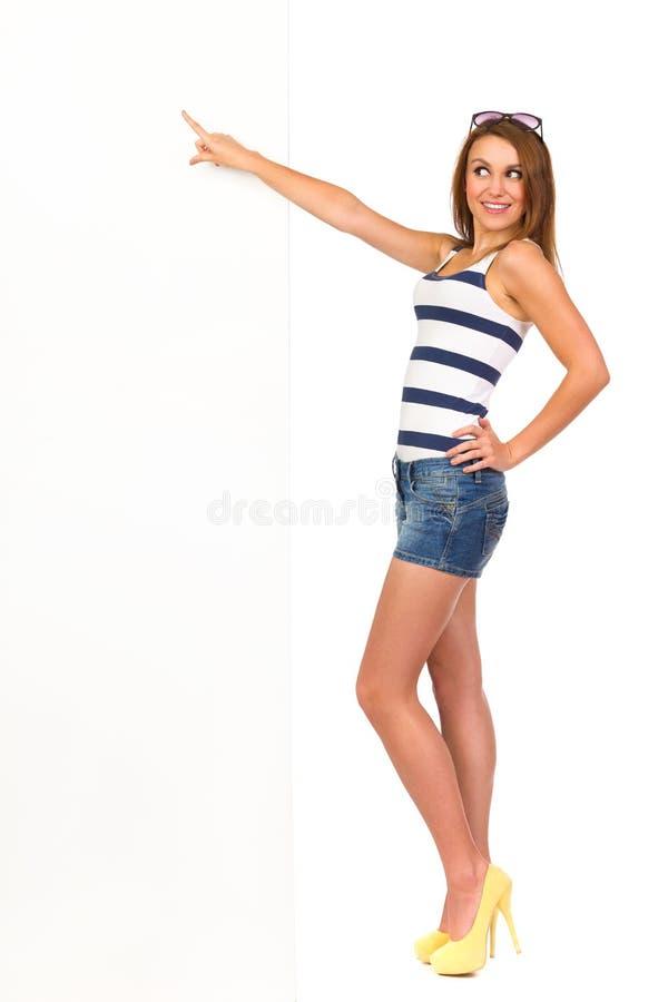 Mujer atractiva sonriente que señala en la bandera. fotografía de archivo