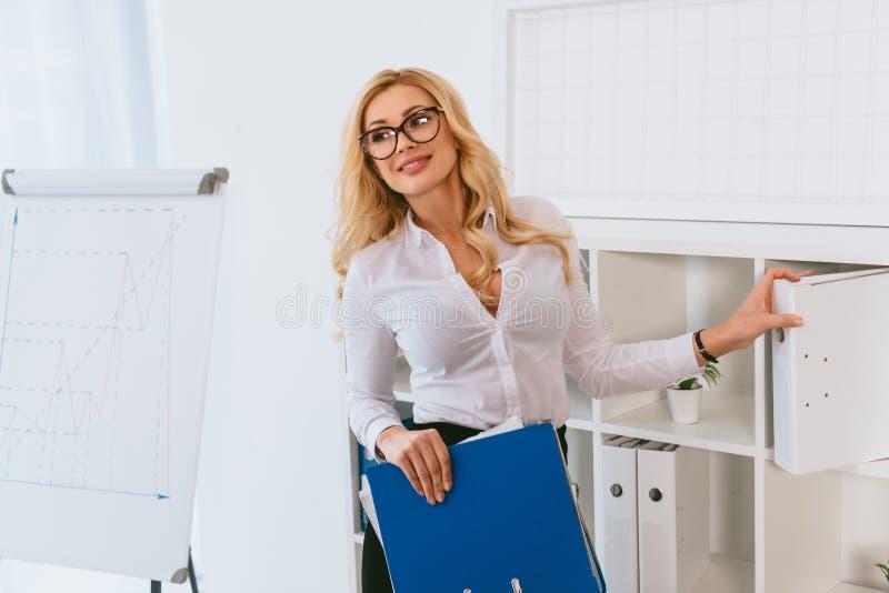 mujer atractiva sonriente que toma carpetas del estante imagen de archivo