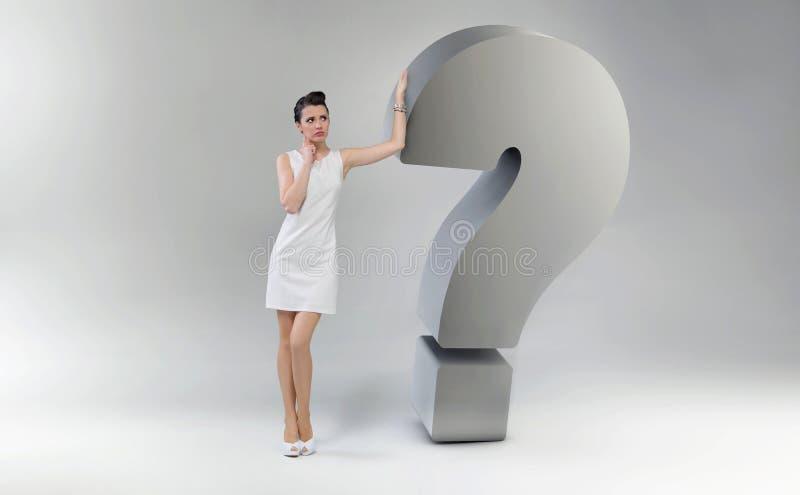 Mujer atractiva y asombrosa que se inclina contra la pregunta marcha fotografía de archivo libre de regalías