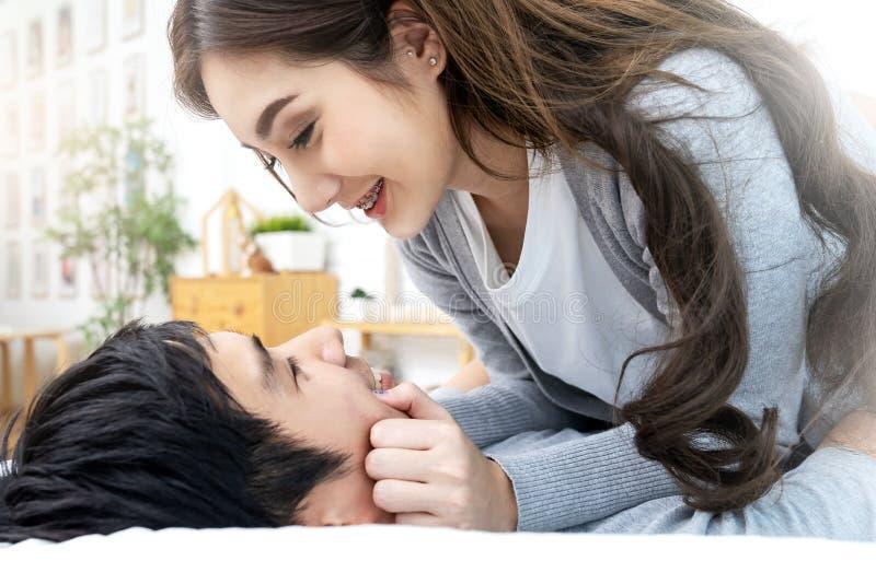 Mujer atractiva y hombre asiáticos jovenes de los pares que sonríen y que mienten en cama así como la sensación de enlace del amo imagenes de archivo