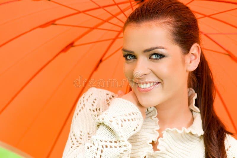Mujer atractiva y paraguas anaranjado foto de archivo libre de regalías