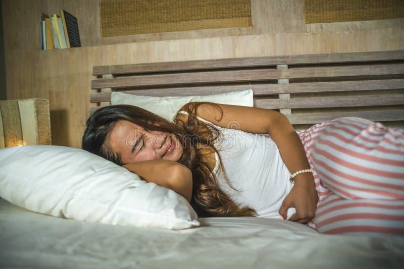 Mujer atractiva y triste joven 20s que miente en dolor sufridor del per?odo de la cama en la expresi?n dram?tica de la cara que t imagenes de archivo