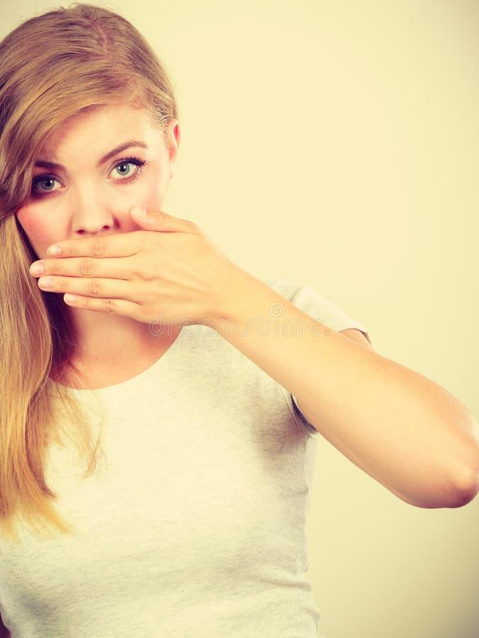 Mujer avergonzada que tiene mano en boca foto de archivo