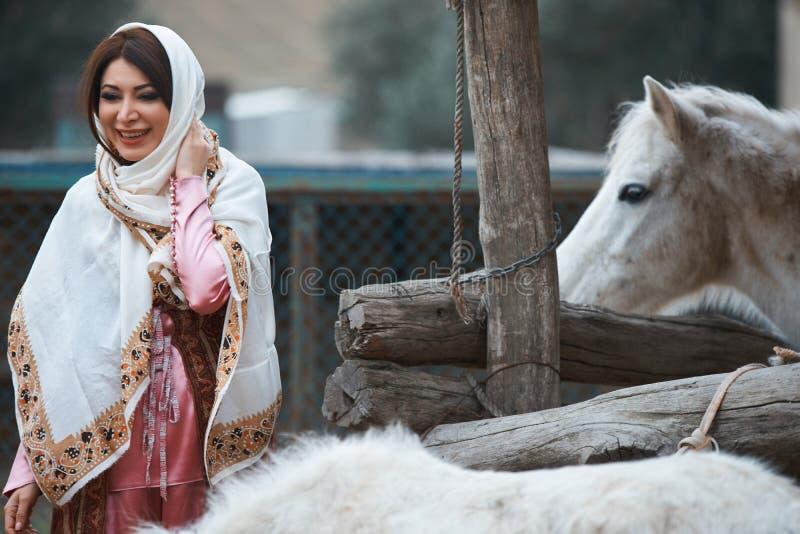 Mujer azerí hermosa en la situación azerbaiyana tradicional del vestido con el caballo blanco imagenes de archivo