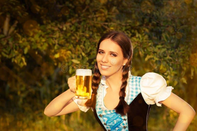 Mujer bávara joven que sostiene la jarra de cerveza de la cerveza imagen de archivo
