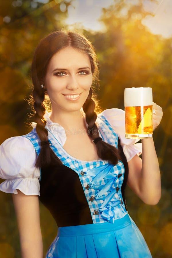 Mujer bávara joven que sostiene la jarra de cerveza de la cerveza foto de archivo libre de regalías