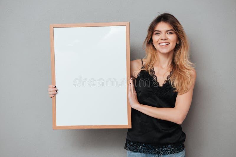 Mujer bastante amistosa que lleva a cabo al tablero en blanco y que mira la cámara fotos de archivo libres de regalías
