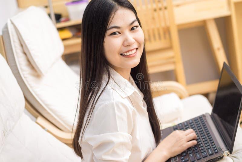 Mujer bastante asiática feliz que usa el ordenador portátil que se sienta en el sofá acogedor imagen de archivo libre de regalías