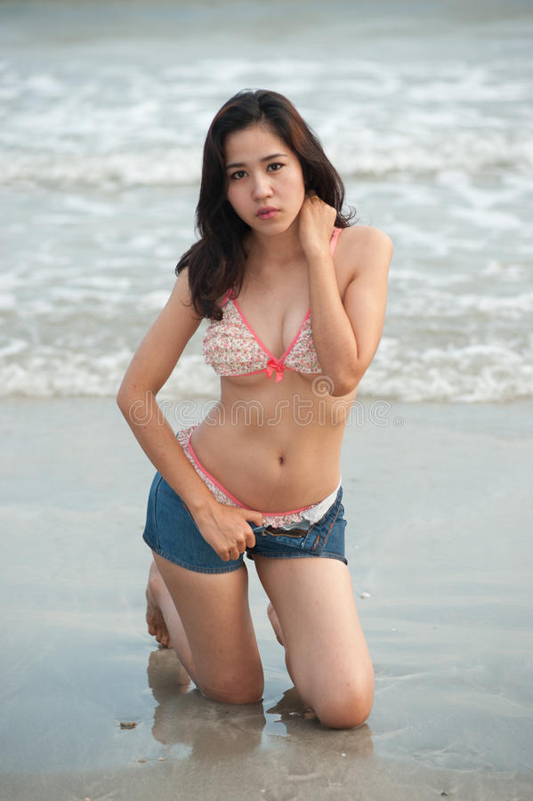 Mujer bastante asiática que presenta en la playa. foto de archivo