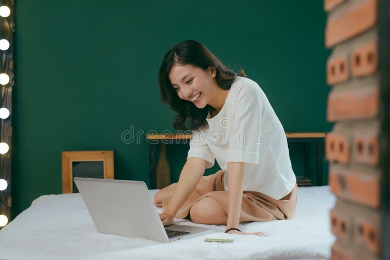 Mujer bastante asiática que usa el ordenador portátil en cama en sitio y smil imágenes de archivo libres de regalías