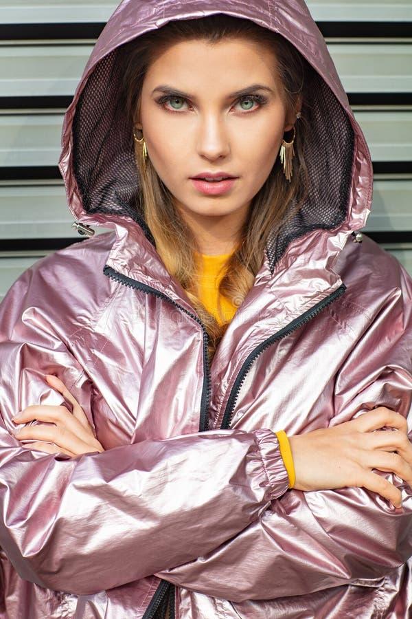 Mujer bastante atractiva y joven que presenta en la calle en ropa colorida imagen de archivo
