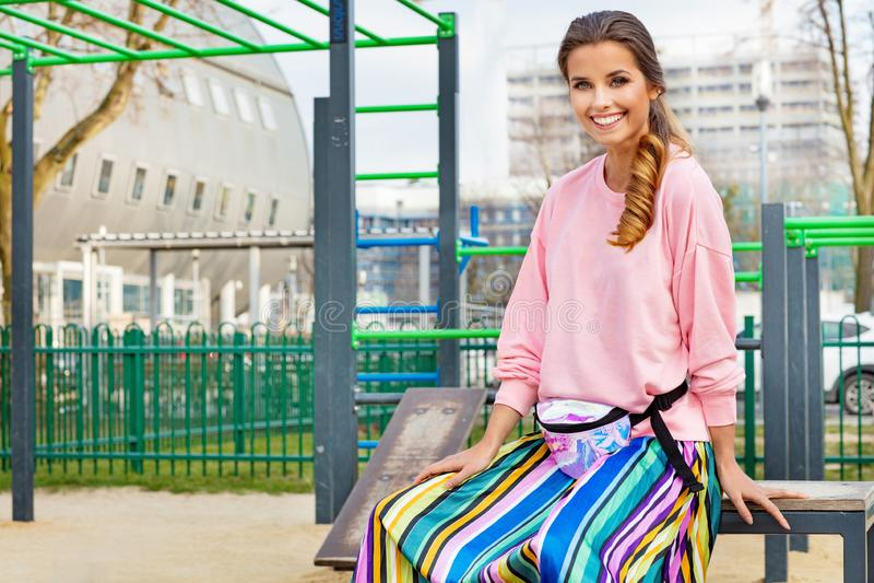 Mujer bastante atractiva y joven que presenta en la calle en ropa colorida imagenes de archivo