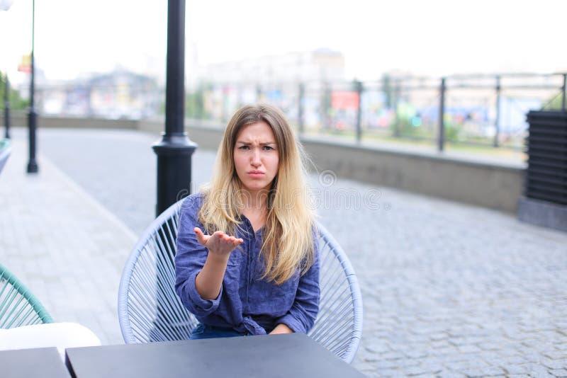 Mujer bastante contrariedad que se sienta en el café de la calle y que hace caras fotografía de archivo
