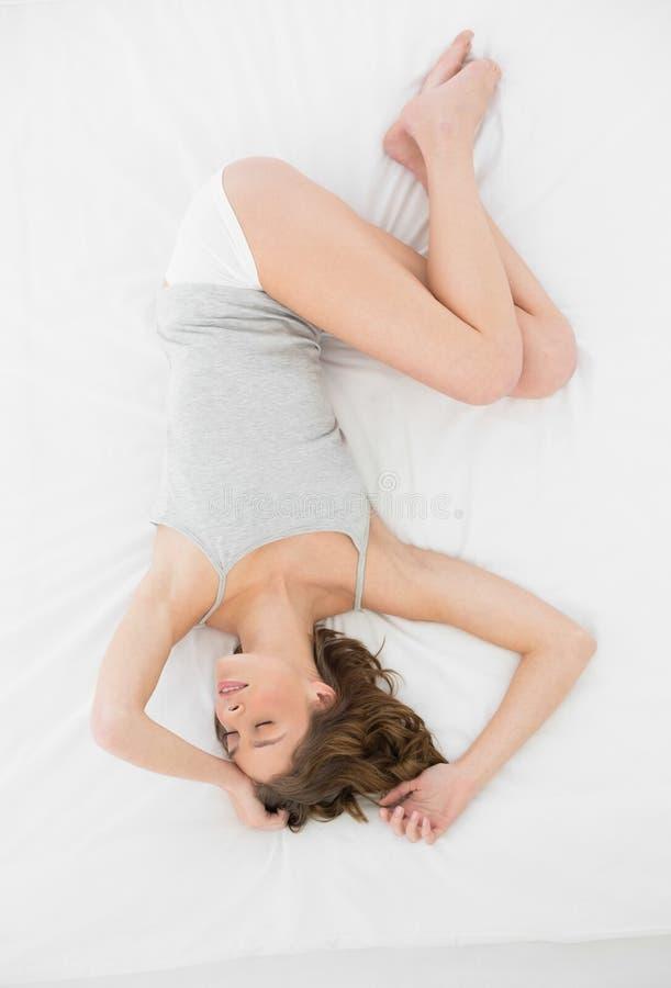 Mujer bastante delgada que miente en la cubierta de su cama mientras que duerme imágenes de archivo libres de regalías