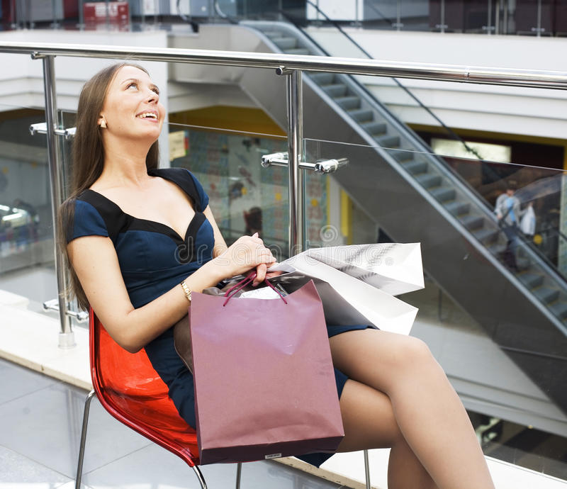 Mujer bastante dulce de los jóvenes con la porción de bolsos en la sonrisa feliz de la alameda de compras, concepto de la gente d fotografía de archivo libre de regalías