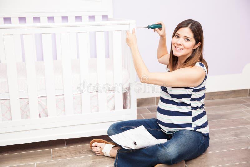 Mujer bastante embarazada que monta un pesebre fotos de archivo