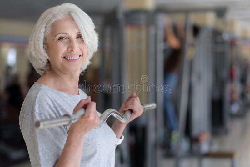 Mujer bastante encantada de Joiful que ejercita con el barbell fotos de archivo